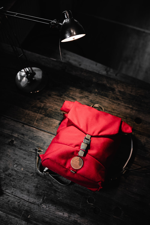 red leather handbag on wooden floor