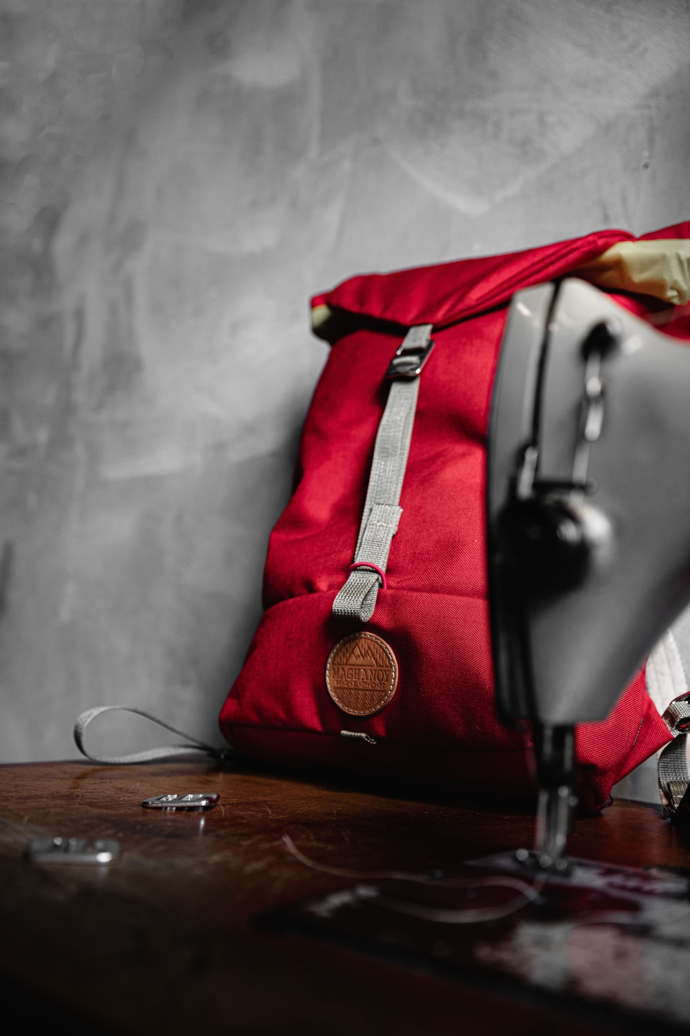 black and red leather handbag on brown wooden table