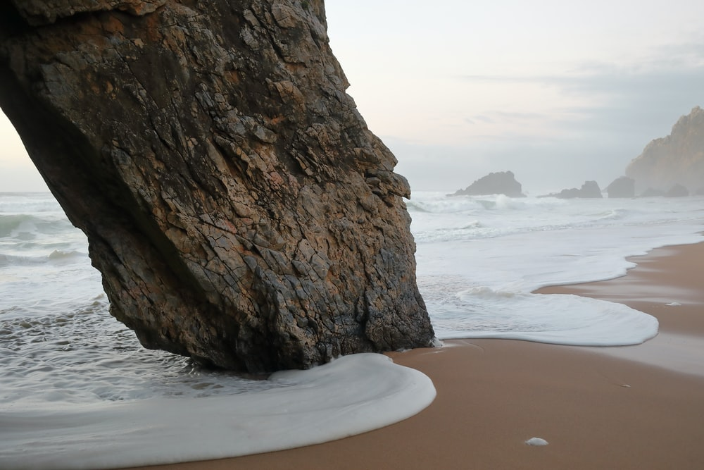 brown rock formation on beach during daytime