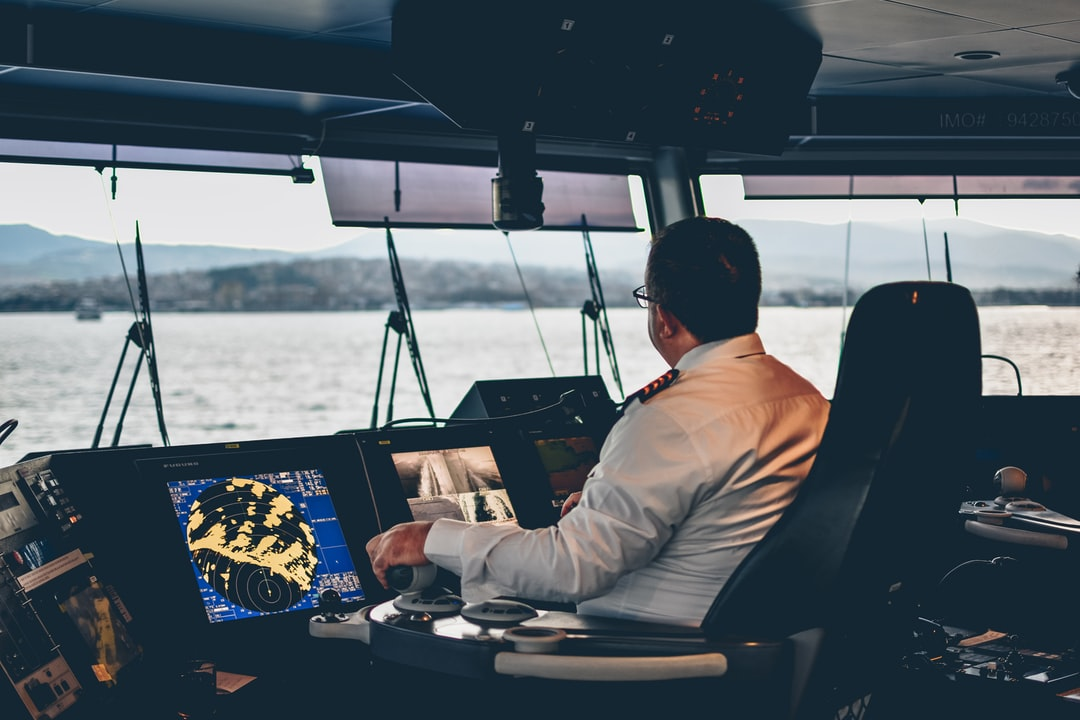 A captain controlling a cruise ferry from the cockpit in the afternoon.