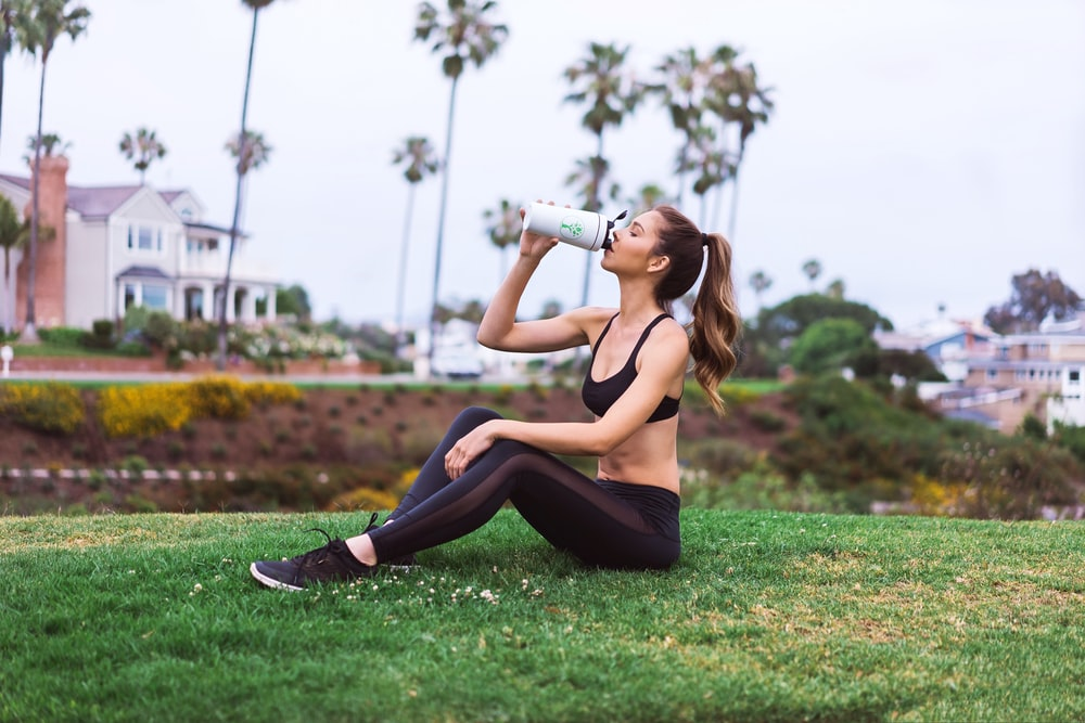 woman in black sports bra and black leggings sitting on green grass field during daytime