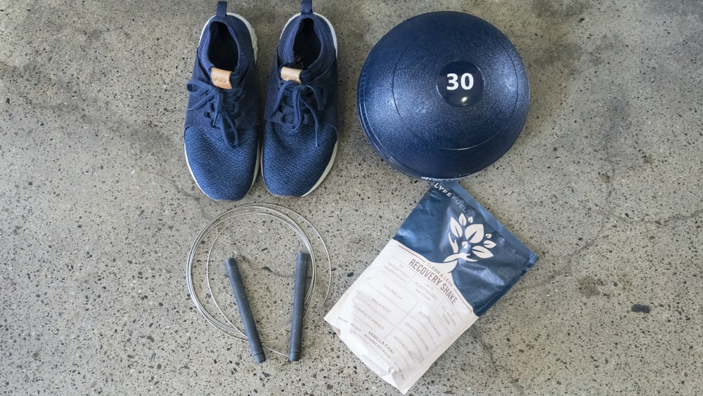 blue and white nike athletic shoes beside black round exercise ball