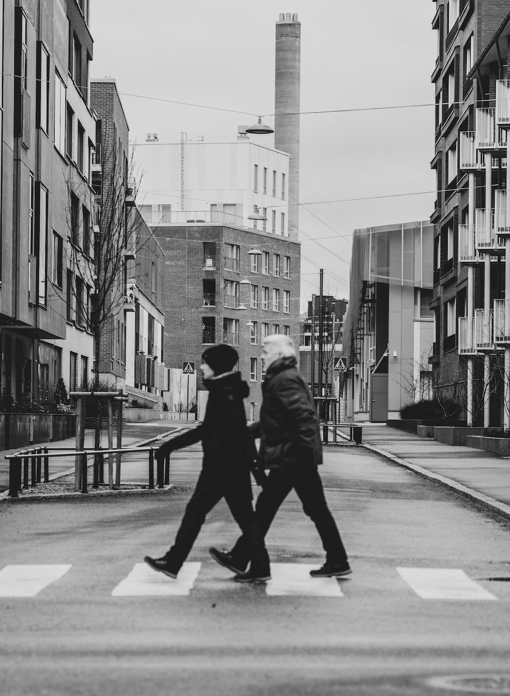 man in black jacket walking on sidewalk in grayscale photography