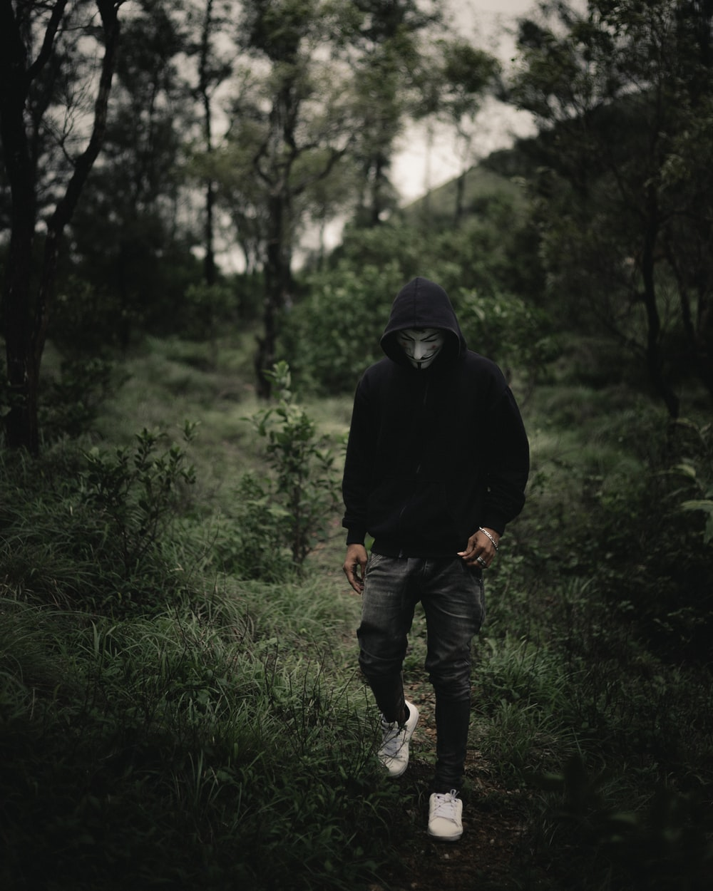 man in black hoodie standing on green grass field during daytime