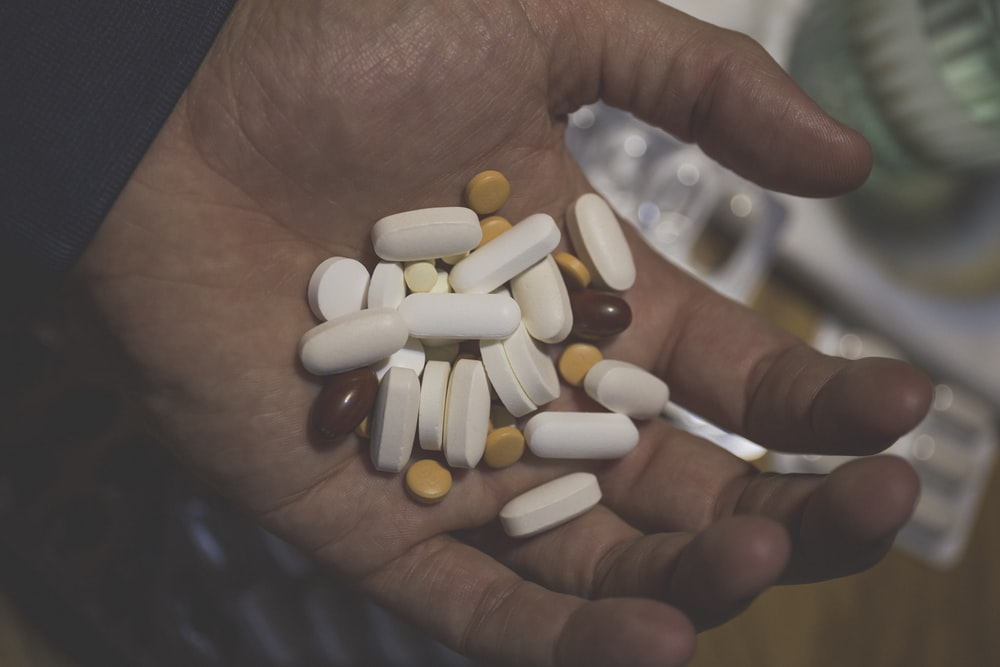 white oval medication pill on persons hand
