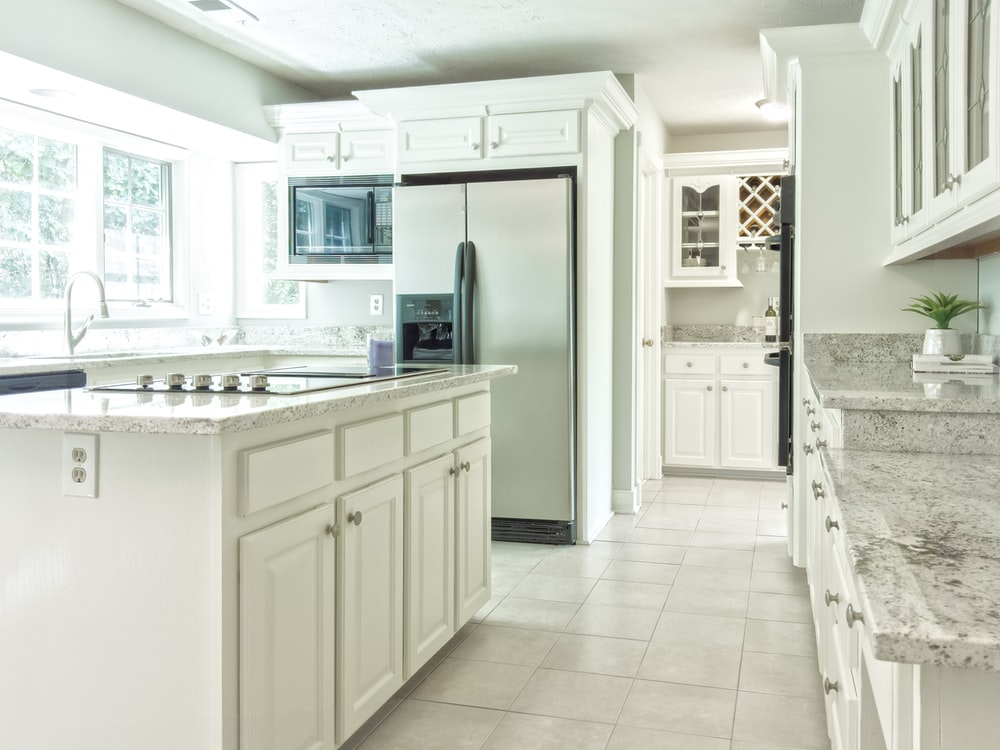white wooden kitchen cabinet near white wooden door