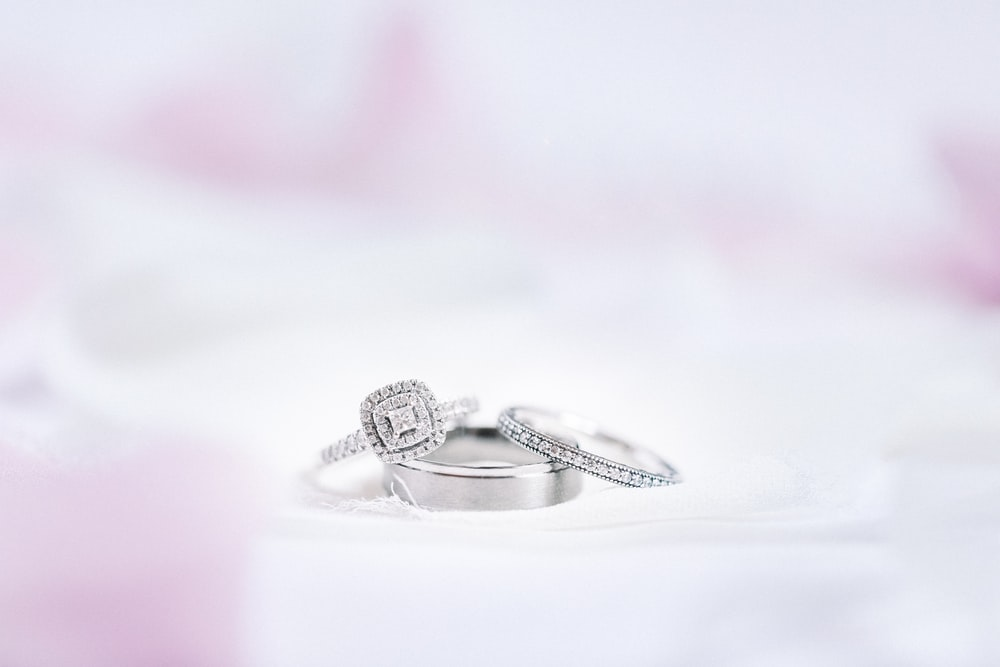 silver diamond studded ring on white surface