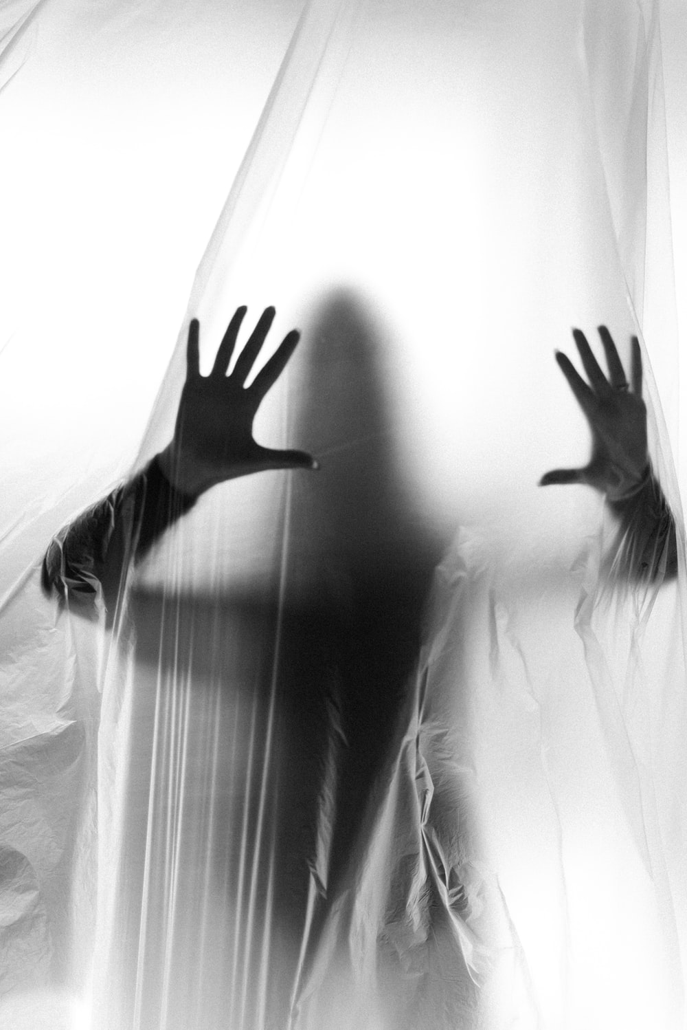grayscale photo of woman raising her hands