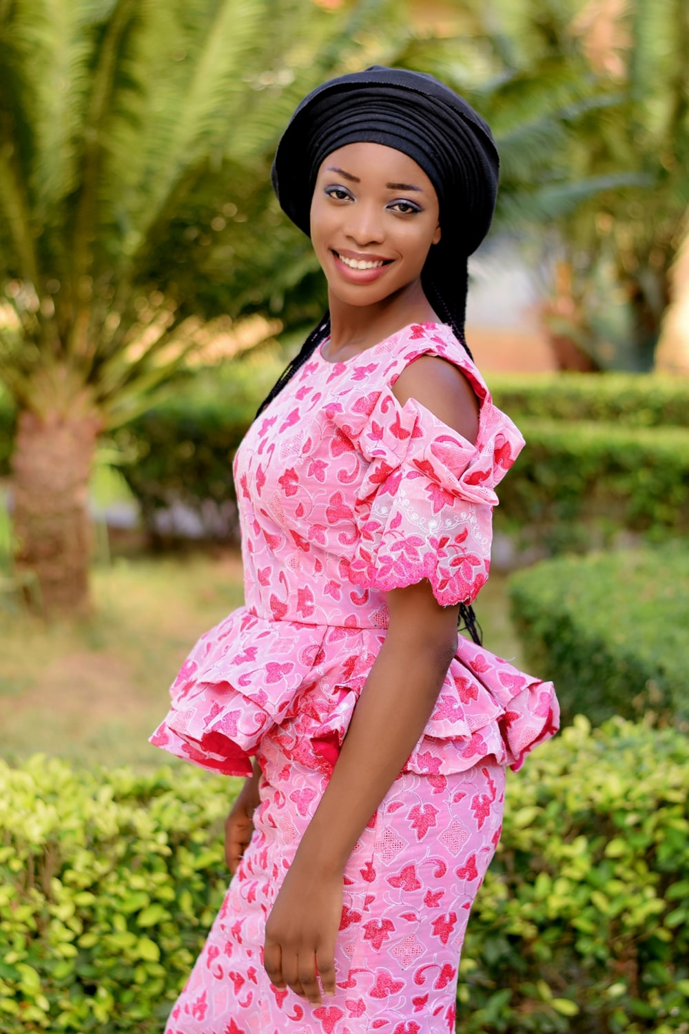 girl in pink and white floral dress standing on green grass field during daytime