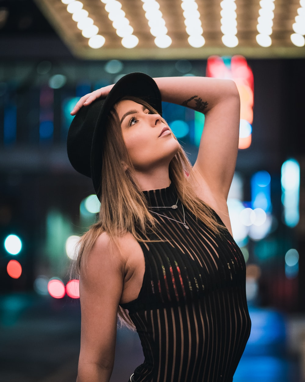 woman in black and white striped tank top wearing black hat
