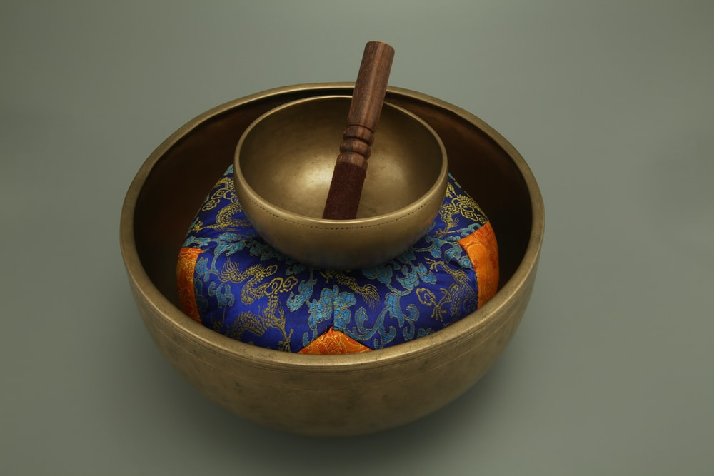 brown wooden mortar and pestle on blue and white floral ceramic bowl