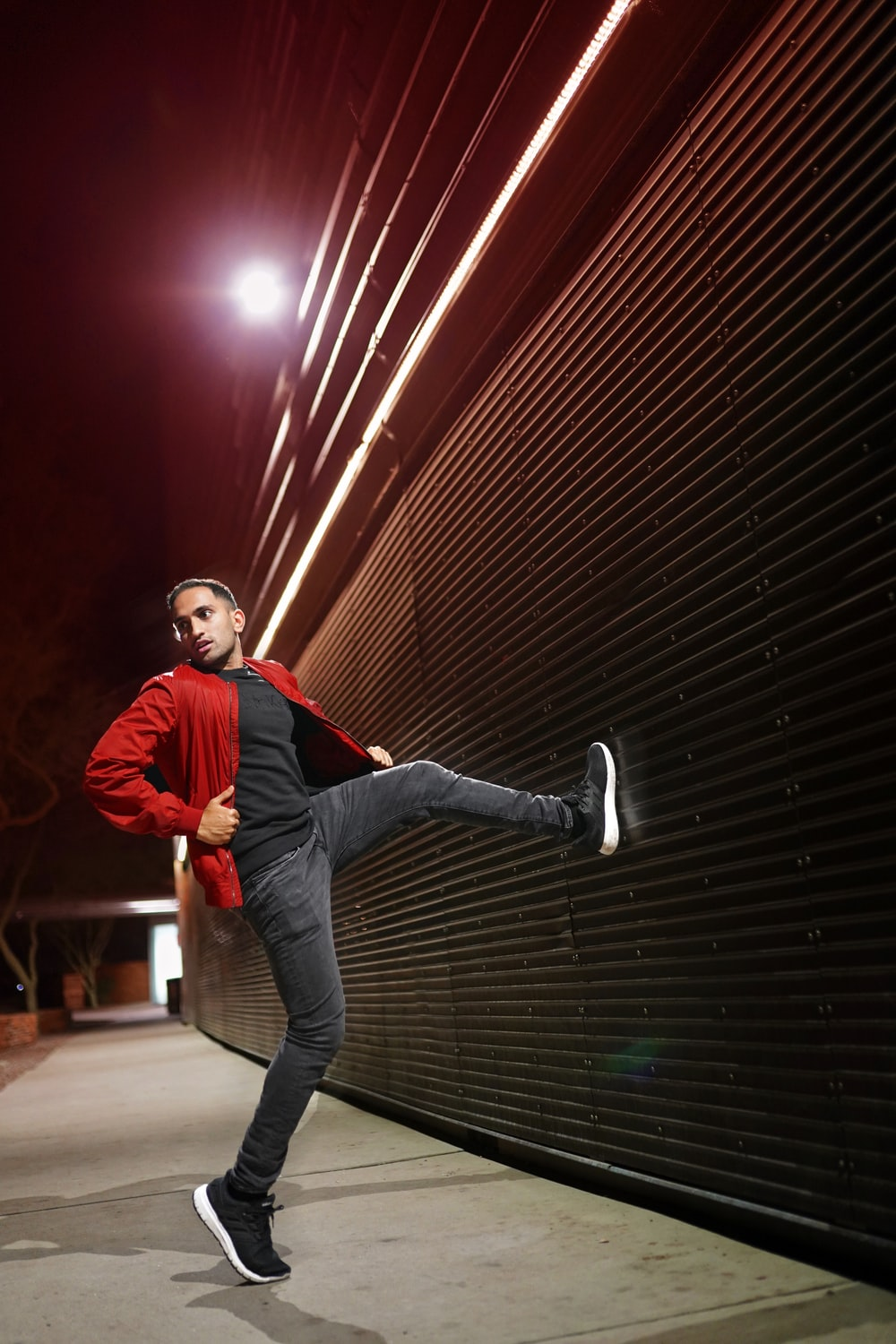 man in red jacket and gray denim jeans jumping