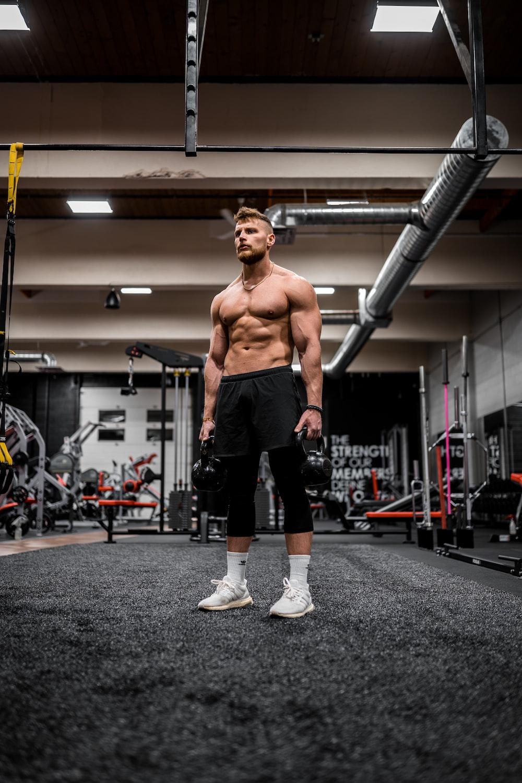 topless man in black shorts and white socks running on gray concrete floor