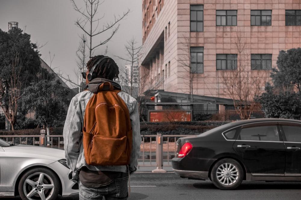man in orange and black jacket standing on sidewalk during daytime