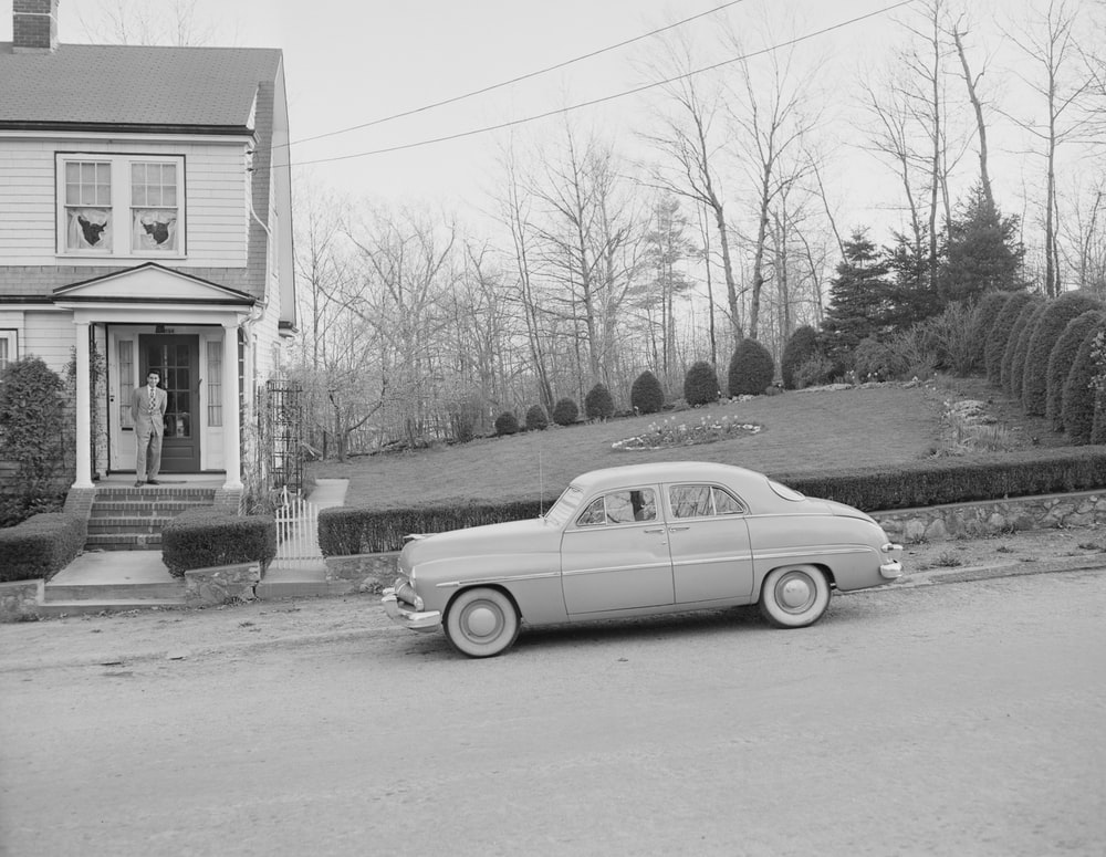 grayscale photo of vintage car parked beside house