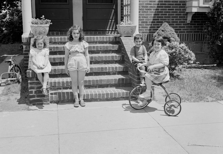 A vintage black and white photo of some children in front of a house. One is riding a tricycle, and the others are posing and smiling.
