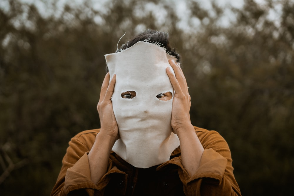 person in brown leather jacket covering face with white face mask