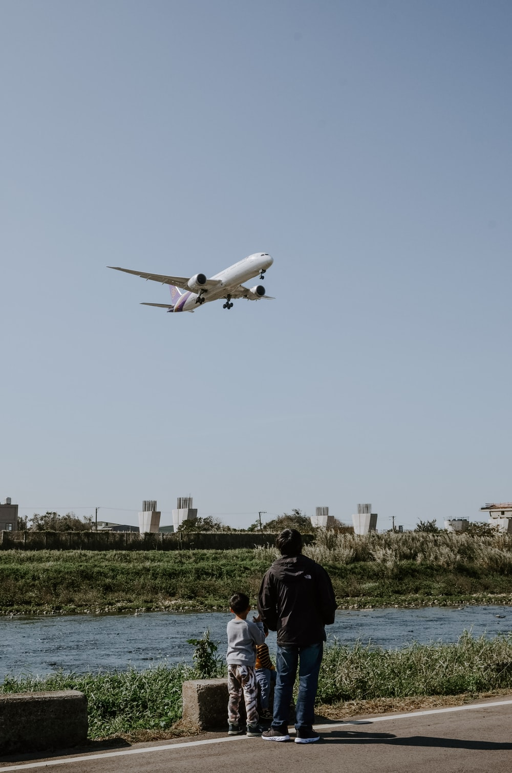 man in black jacket standing near white airplane during daytime