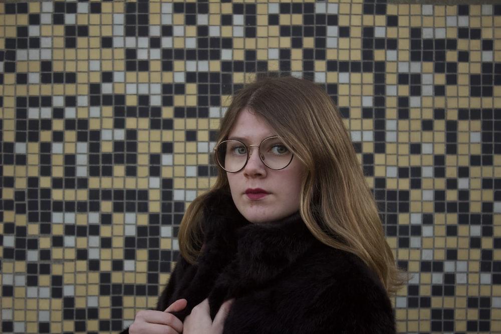 woman in black fur coat wearing black framed eyeglasses