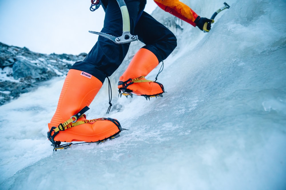 person in orange and black snow goggles and black and white jacket on snow covered ground