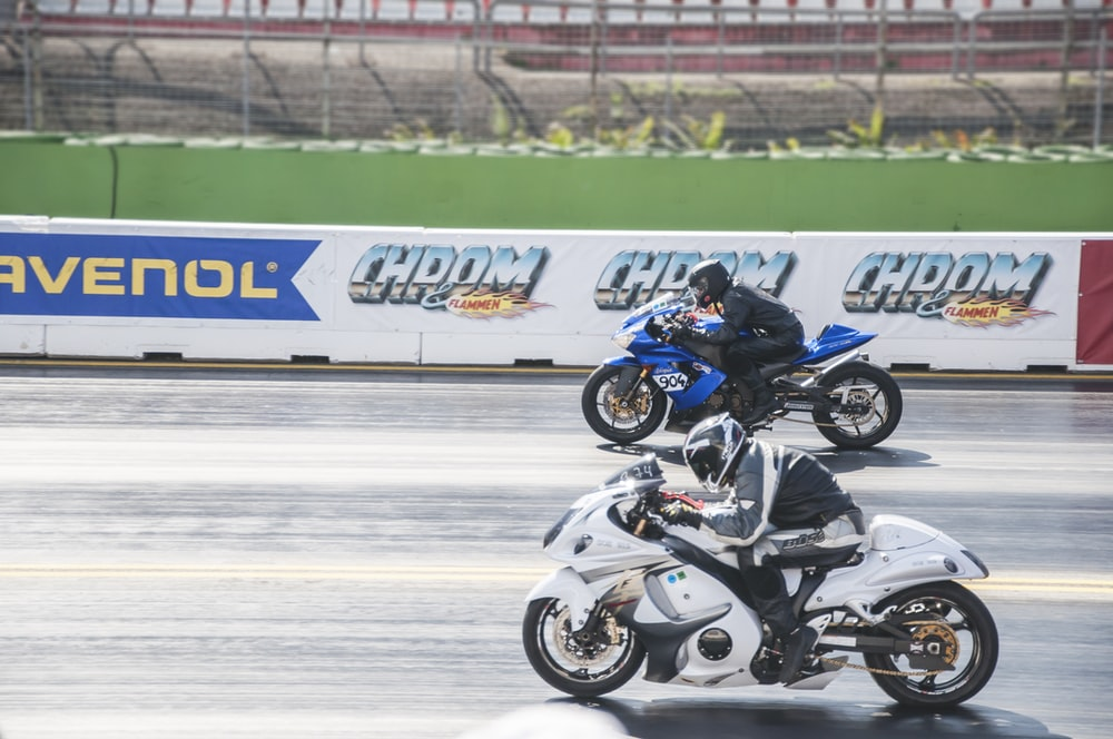man in black and white motorcycle suit riding on white and blue sports bike
