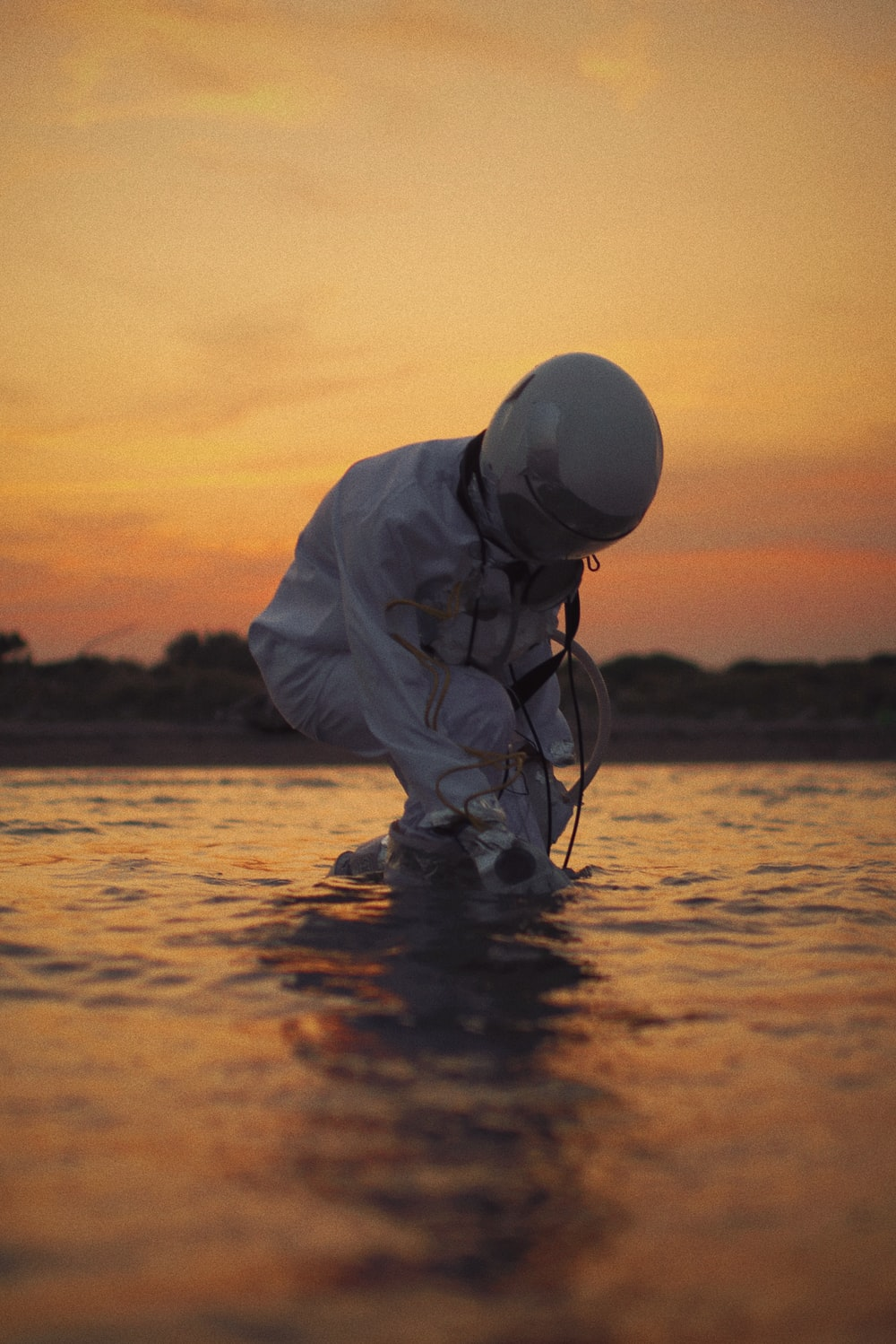 man in white dress shirt and black pants fishing on sea during sunset