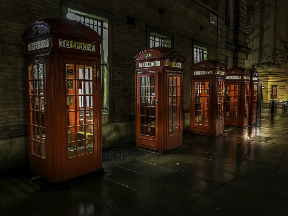 red telephone booth on brown brick floor