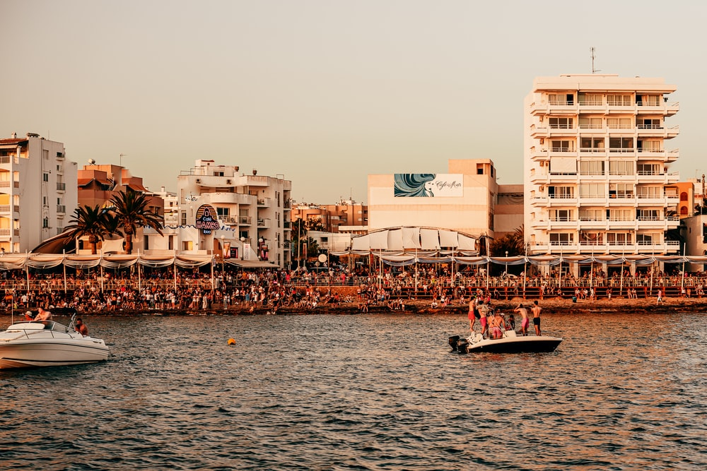 people riding on boat on sea near buildings during daytime, Ibiza sunset strip