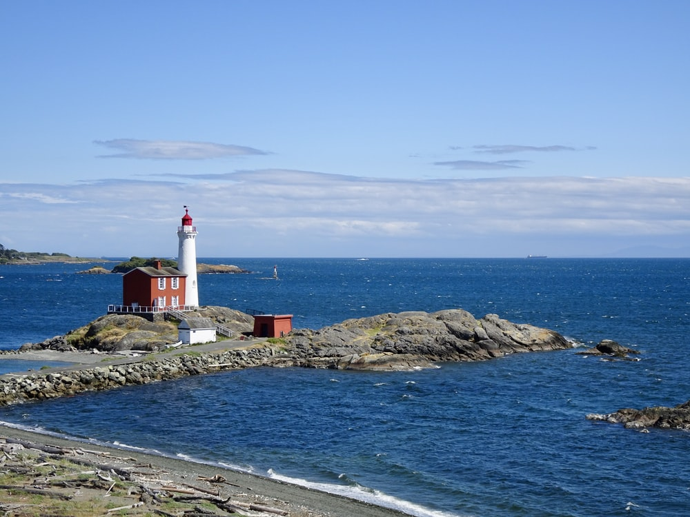white and red lighthouse on rocky shore during daytime