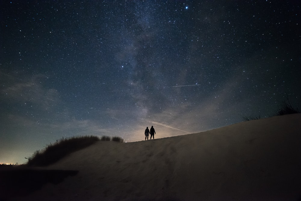 2 person walking on snow covered ground under starry night