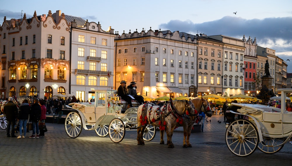 people riding on horse carriage near building during daytime