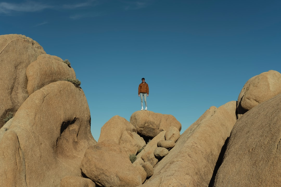 Man In Brown T-Shirt and White Shorts Standing On Brown Rock Formation Under Blue Sky - unsplash