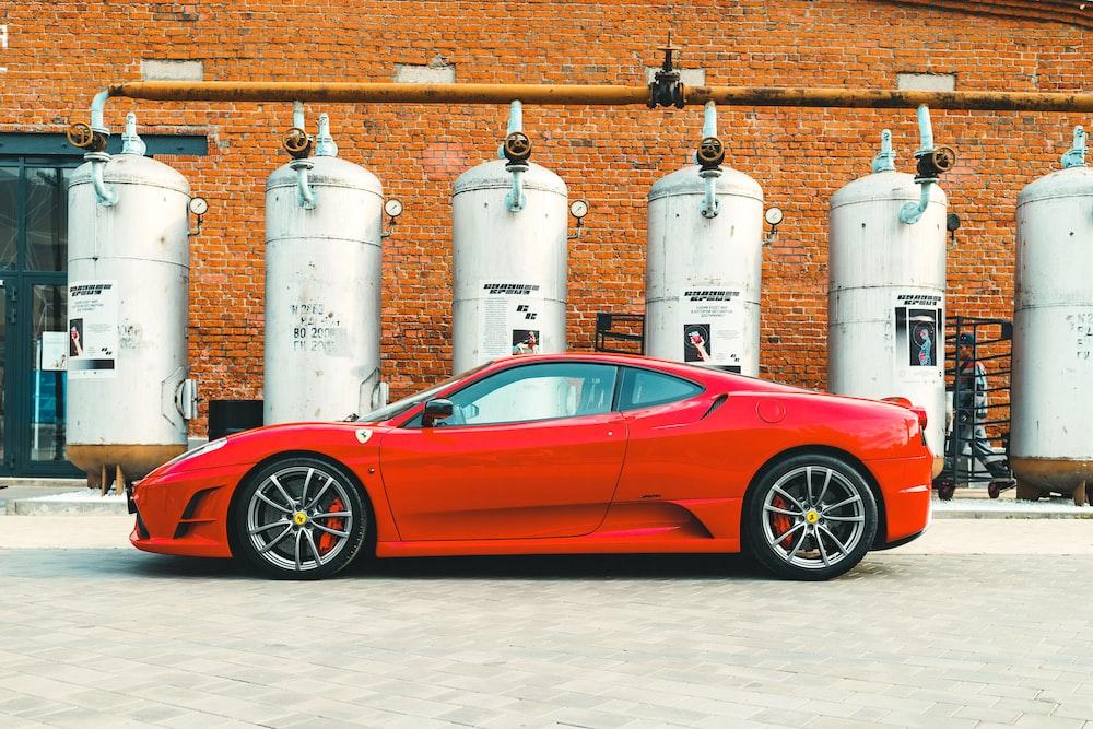 red ferrari 458 italia parked beside white propane tank