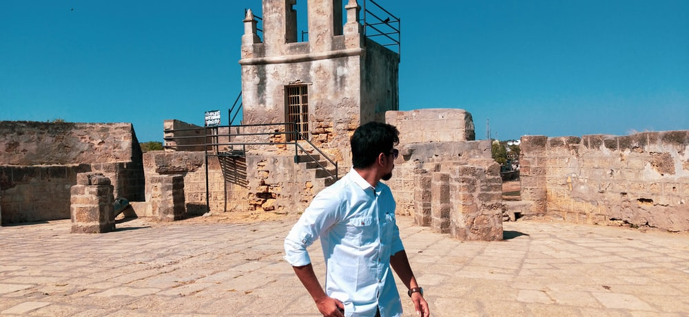 man in white t-shirt standing near brown concrete building during daytime