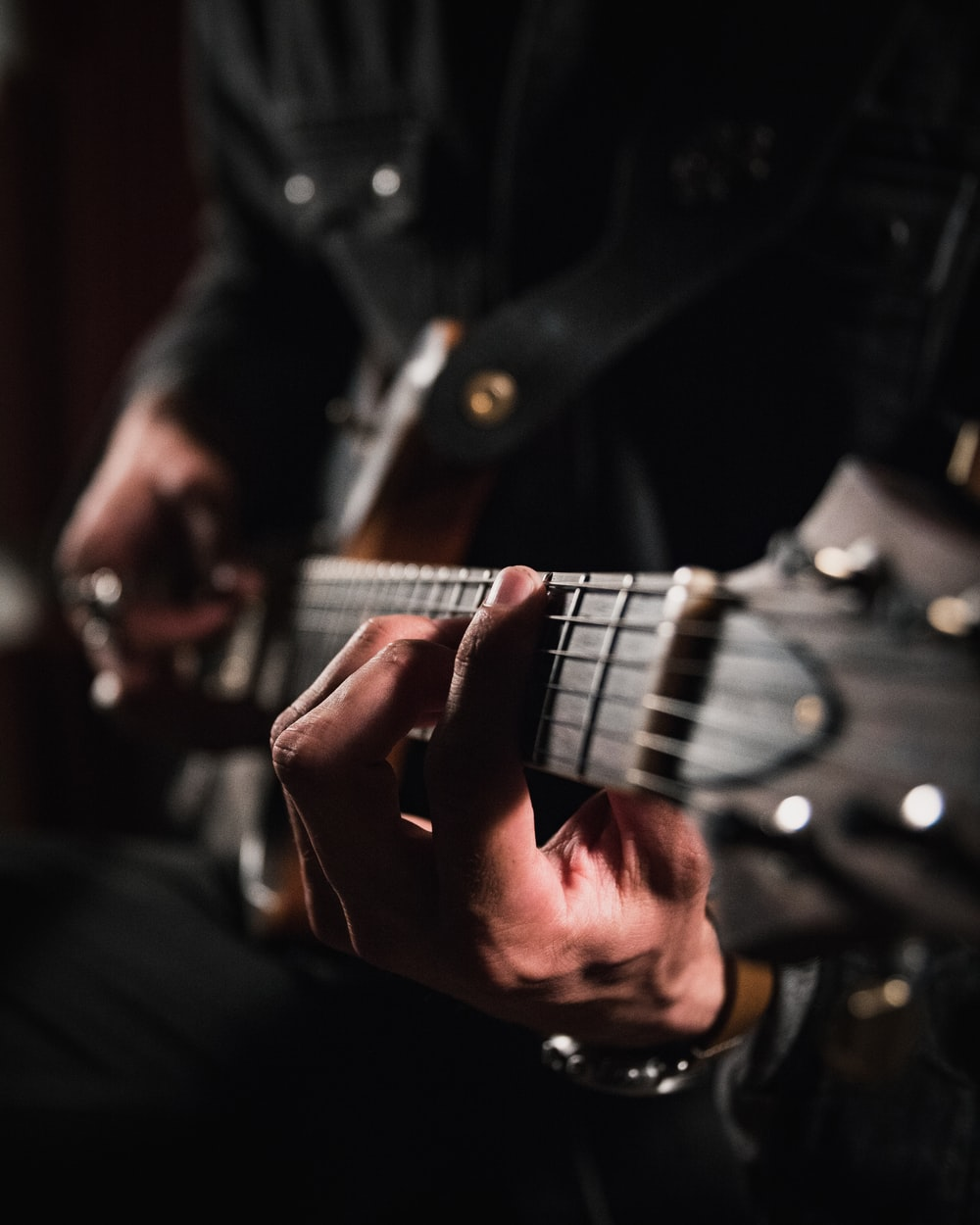man playing guitar in close up photography