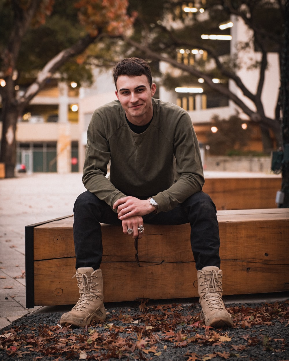 man in gray sweater sitting on brown wooden bench during daytime