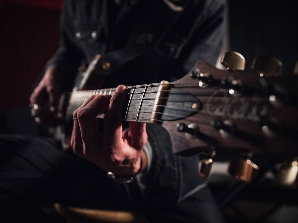 man in black jacket playing guitar