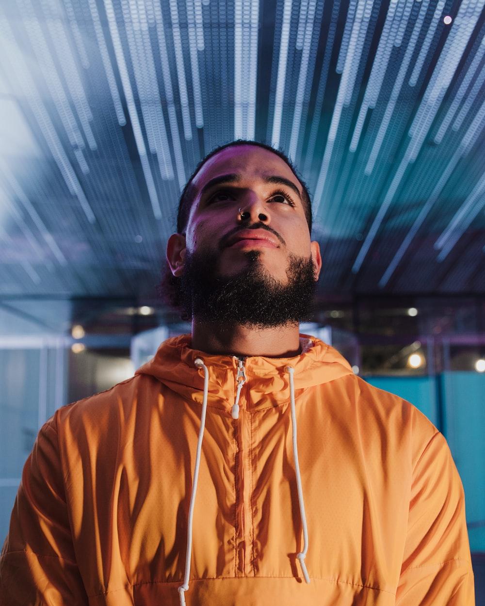 man in orange hoodie standing