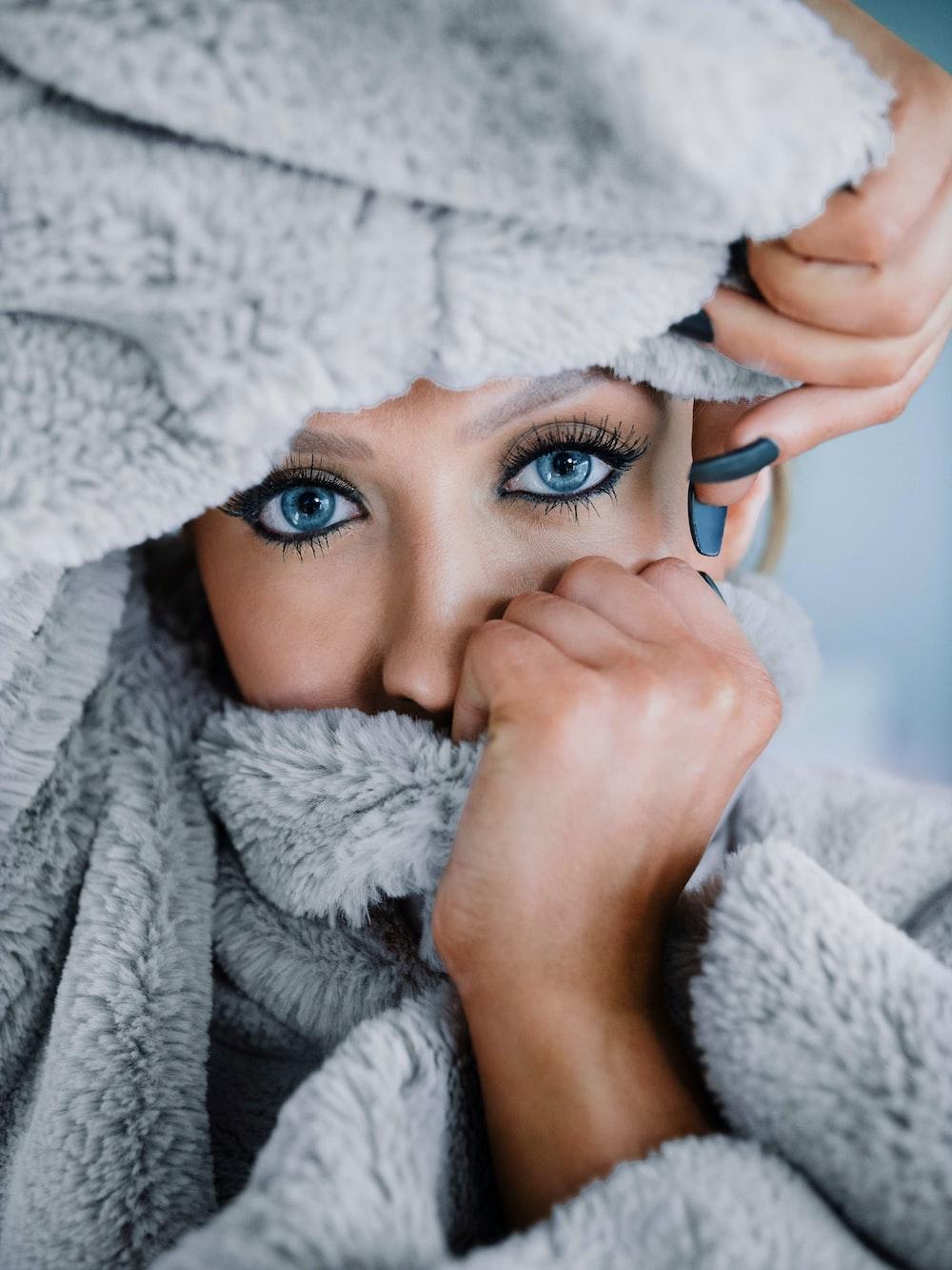 woman in white bath robe holding blue ceramic mug