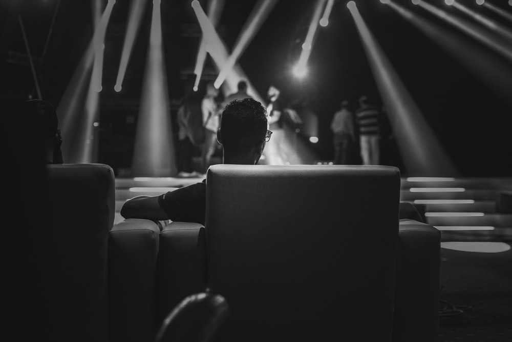 grayscale photo of people sitting on chair