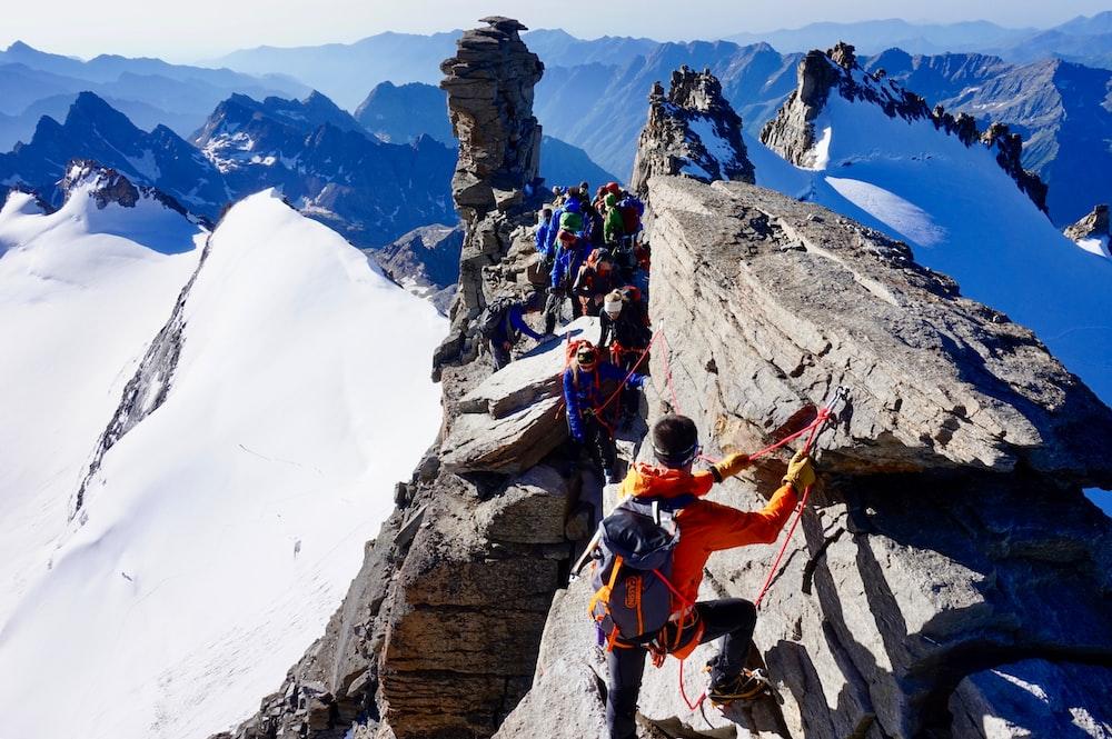 man in orange jacket climbing on mountain during daytime