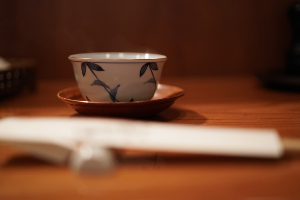white and blue ceramic bowl on brown wooden table