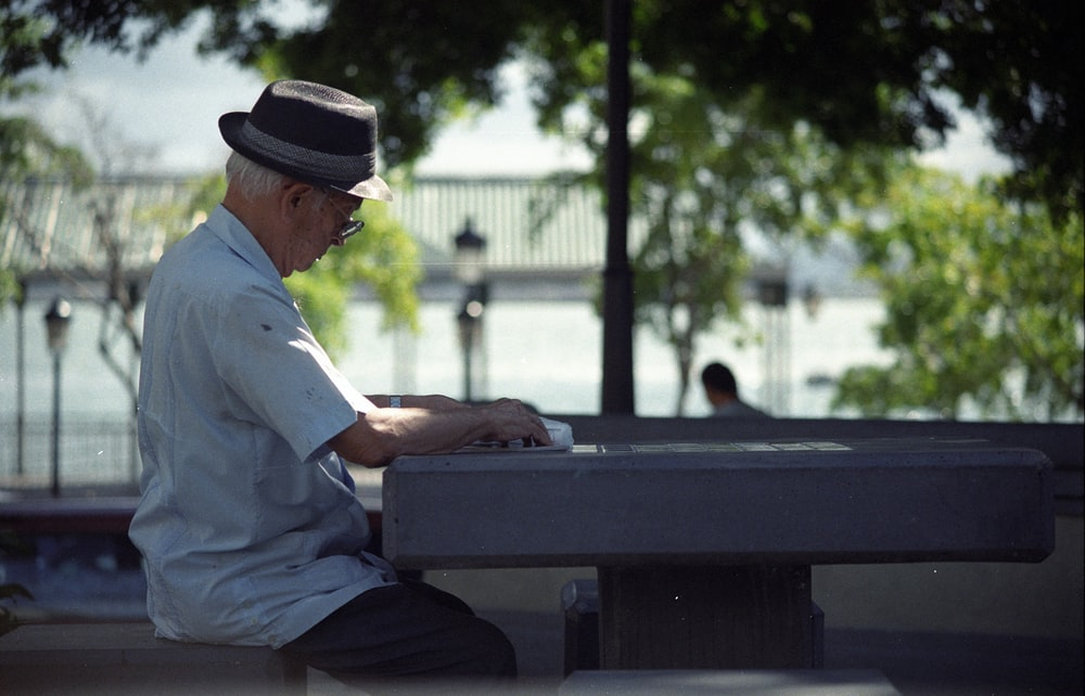 man in white dress shirt and black fedora hat sitting on bench