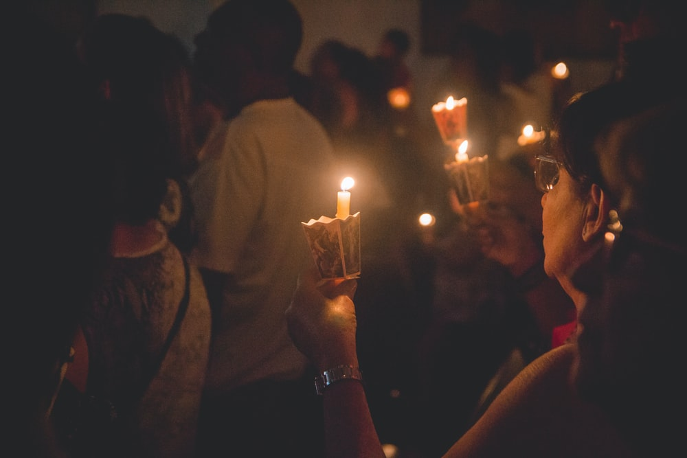 people holding lighted candles during nighttime