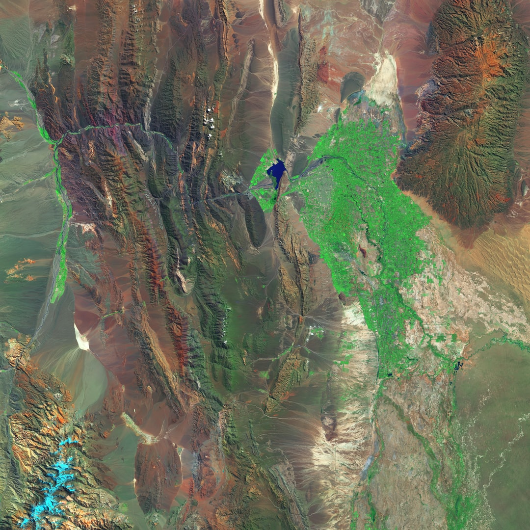"""San Juan, Argentina, nestles in a fertile valley flanked by arid mountains. Croplands and vineyards (green) abut the metropolitan area on the San Juan River. The white """"teardrop"""" (lower left) is an ancient lakebed called Barreal Blanco. It is one of the best places in the world for carrovelismo, or landsailing, thanks to the steady winds that sweep across this flat, unobstructed expanse of hard-packed sediment."""