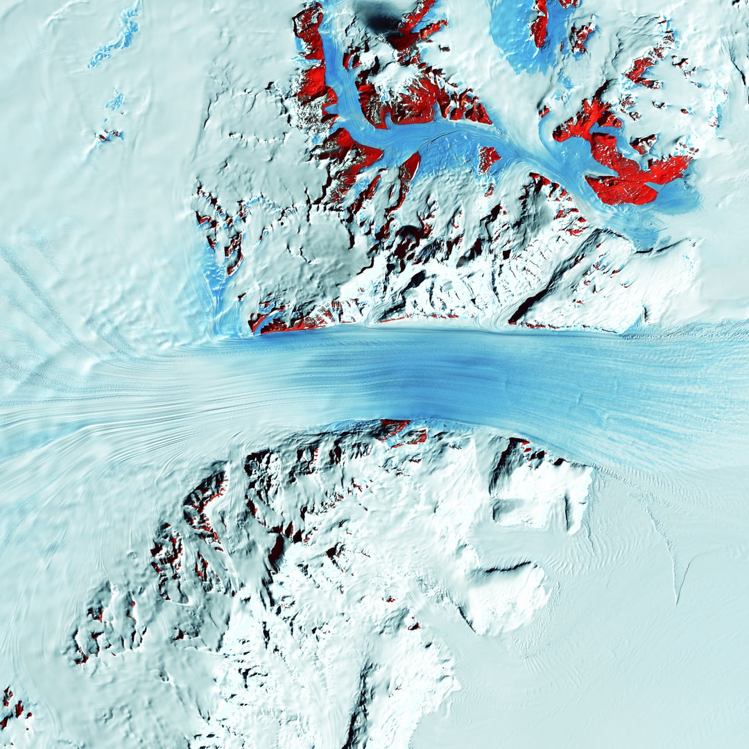 Truly a river of ice, Antarctica's relatively fast-moving Byrd Glacier courses through the Transantarctic Mountains at a rate of 0.8 kilometers (0.5 miles) per year. More than 180 kilometers (112 miles) long, the glacier flows down from the polar plateau (left) to the Ross Ice Shelf (right). Long, sweeping flow lines are crossed in places by much shorter lines, which are deep cracks in the ice called crevasses. The conspicuous red patches indicate areas of exposed rock.