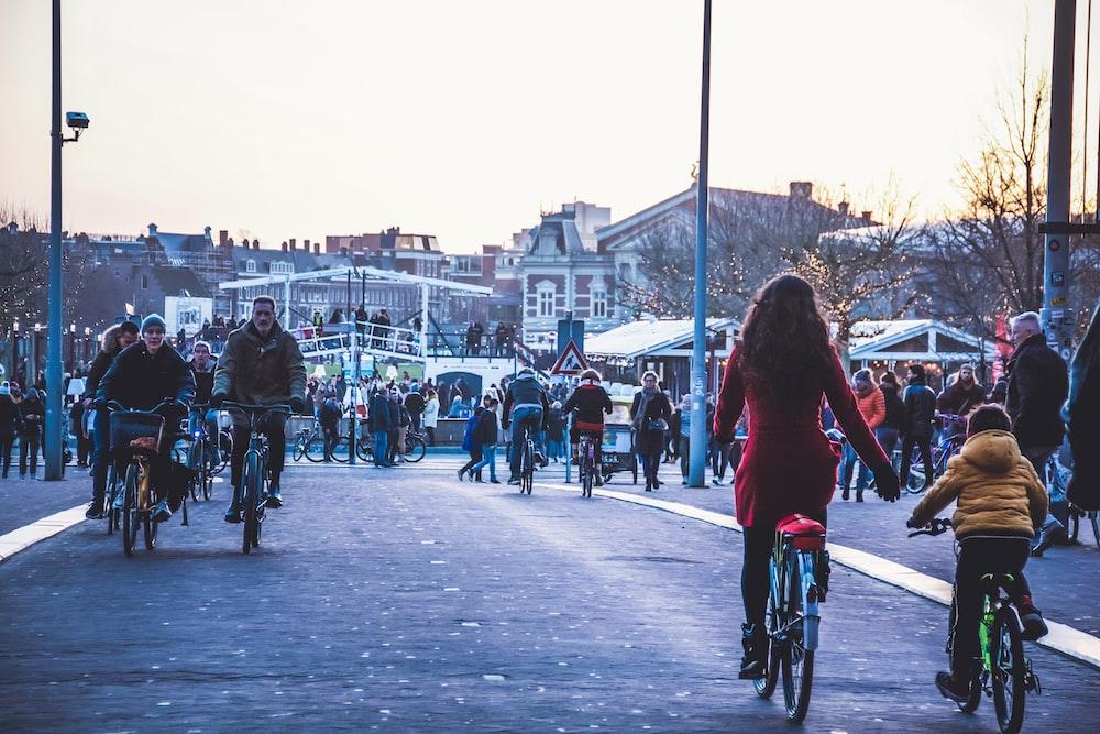 people riding bicycle on street during daytime