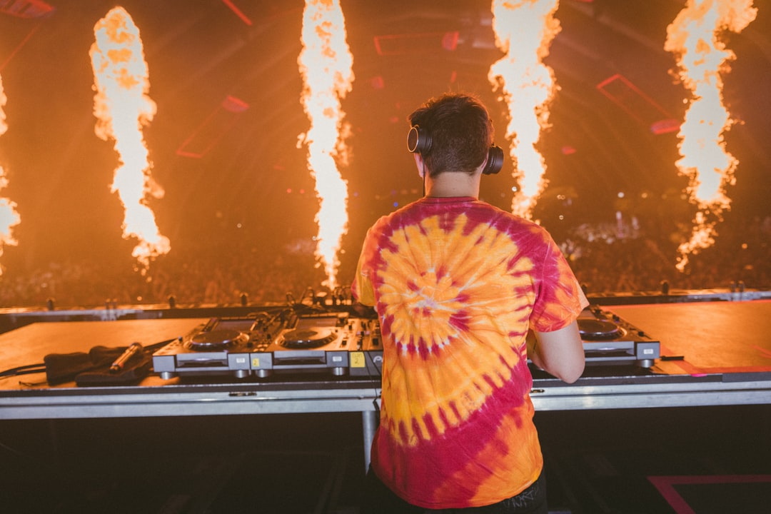 Man In Red and Yellow Tie Dye Shirt Standing In Front of Dj Controller - unsplash