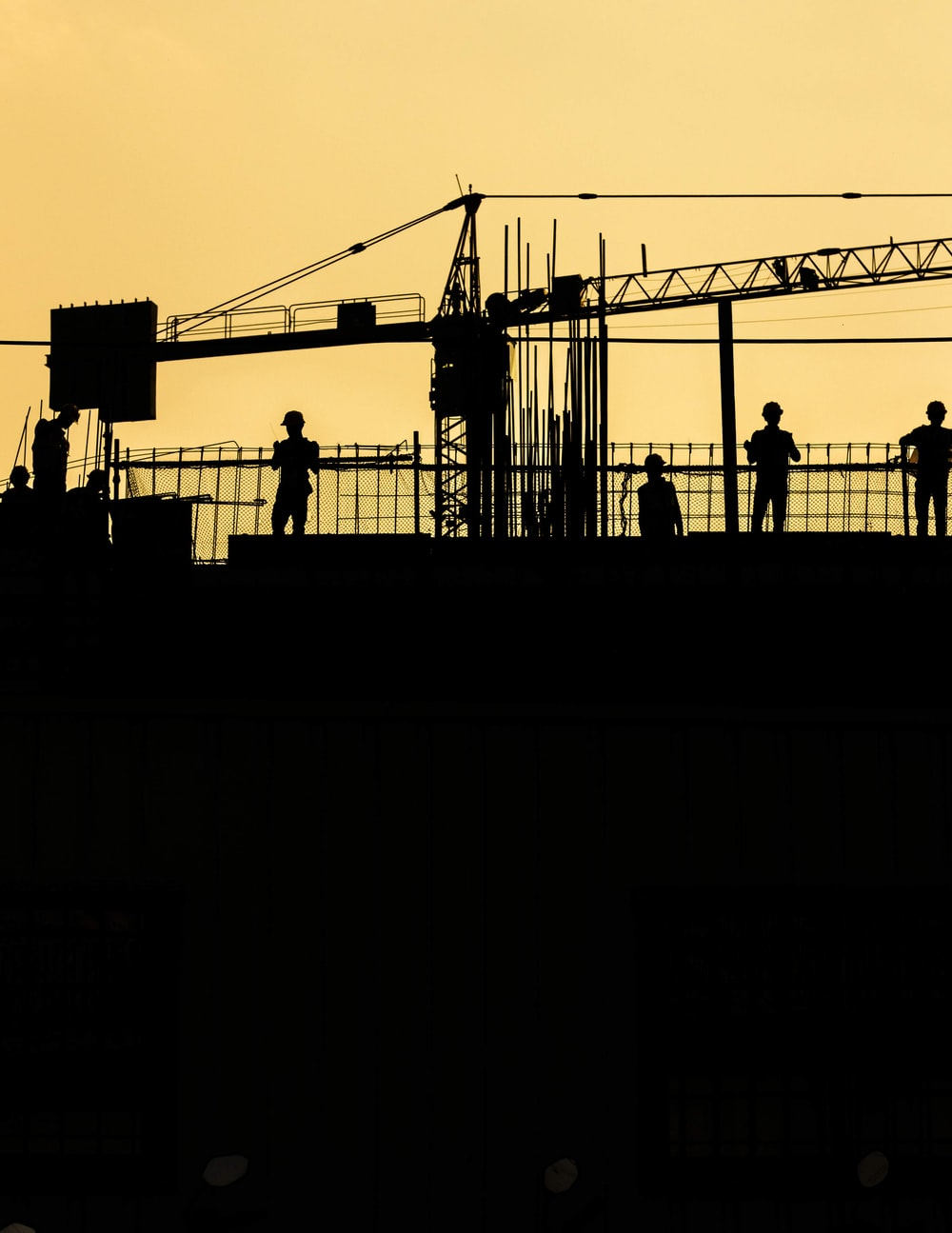 silhouette of people standing on tower crane during night time