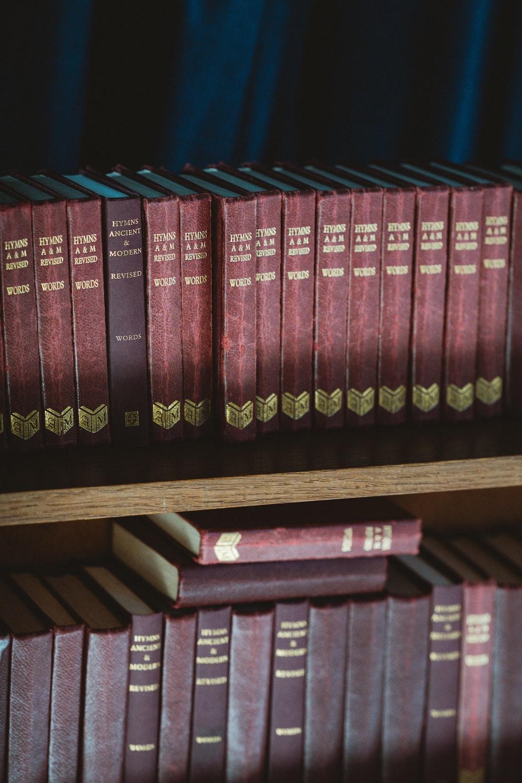 red and black hardbound books on brown wooden shelf
